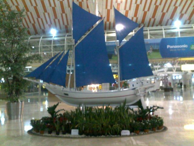 Model kapal pinisi di dalam bandara.