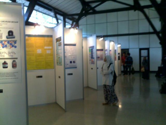 Pengunjung sedang melihat-lihat pameran poster