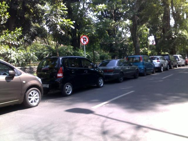 Kondisi Jalan Ganesha dengan parkiran mobil-mobil mahasiswa di areal rambu larangan parkir.