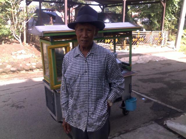 Aki Jupri dengan latar belakang gerobaknya