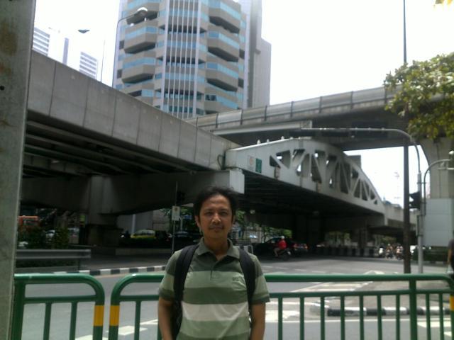 Saya dengan latar belakang jalan jalur layang kereta api Skytrain