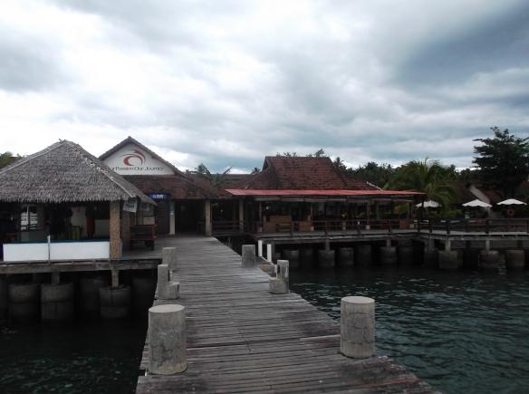 Resor butik CocoTinos dengan dermaga kayu ke tengah laut.