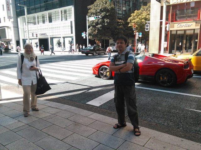 Mobil-mobil mewah berseliwera di Ginza. Mejeng di depan mobil Ferari.