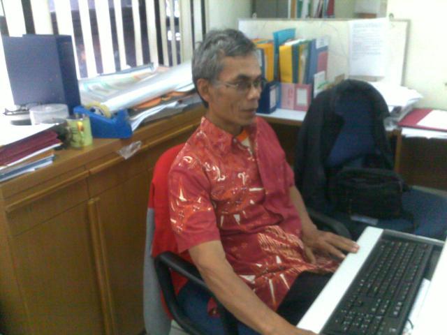 Pak Rasidi di depan meja kerjanya.