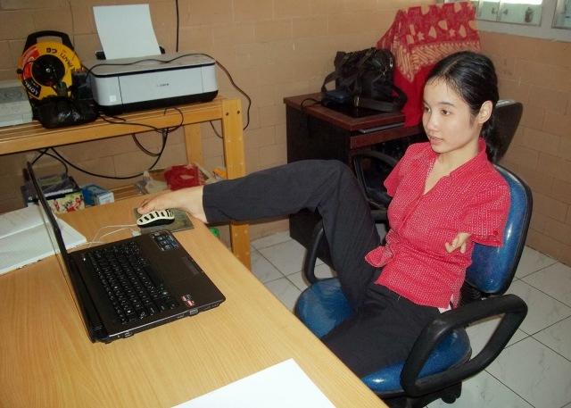 Putri Herlina menggunakan komputer dengan kedua kakinya. (Sumber: http://saptuari.blogspot.com/2013/10/tuhan-maha-sutradara.html)