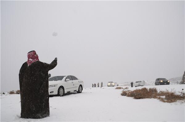 Seorang Arab di hamparan salju di daerah Tabuk, Arab saudi (Sumber: http://www.republika.co.id/berita/internasional/global/13/01/14/mgepyh-salju-turun-di-padang-pasir-arab-saudi)