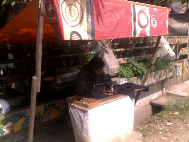 Pak Ajun setia mangkal di pinggir Jalan Kuningan Raya dengan mesin jahit setianya.