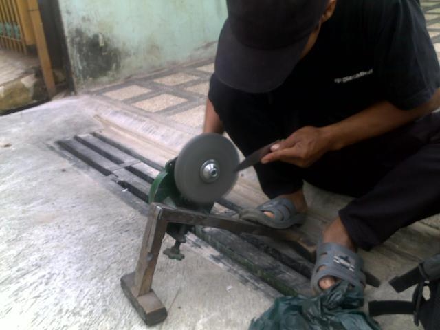 Mang Tata sedang tekun mengasah psiau dengan batu gerinda yang berputar