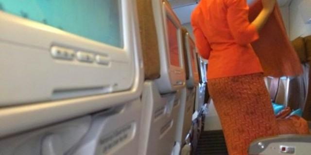 Pramugari Garuda Indonesia mengambil sesuatu seperti kain dari tasnya.