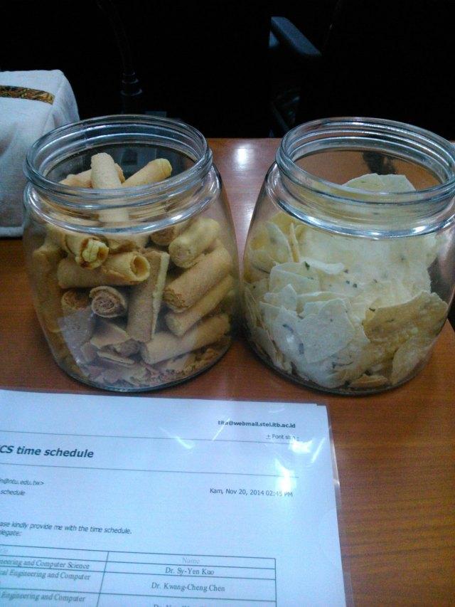 Hidangan kerupuk ubi dan kue semprong di atas meja rapat di kantor fakultas.
