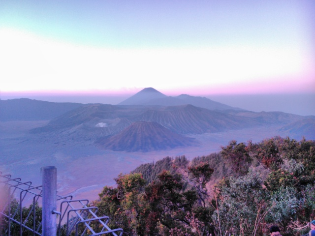 Tiga buah puncak Gunung dengan lautan pasir di bawahnya.  Gunung Batok di latar depan, di sebelahnya Gunung Bromo dengan kawahnya, dan di belakangnya Gunung Semeru.