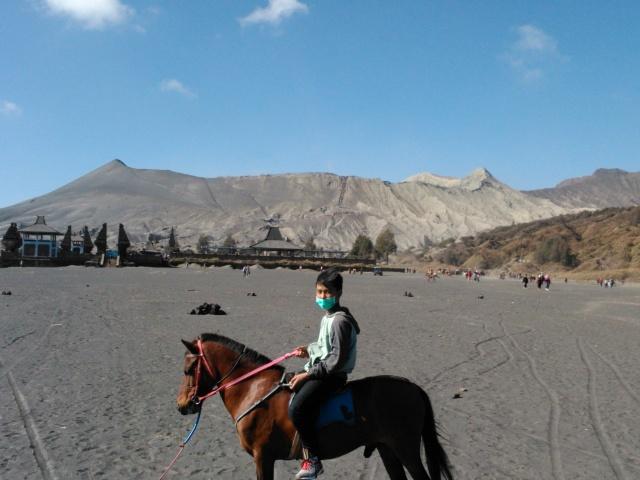 Anak saya befoto ddengan latar belakang Gunung Bromo. Di kaki Guunung Bromo terlihat sebuah pura.