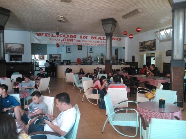 Welkom in Malang dan kursi-kursi rotan rendah di dalam toko Oen