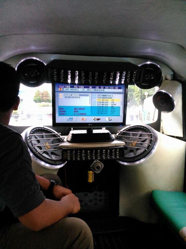 Sound system dan layar komputer di dashboard belakang angkot.